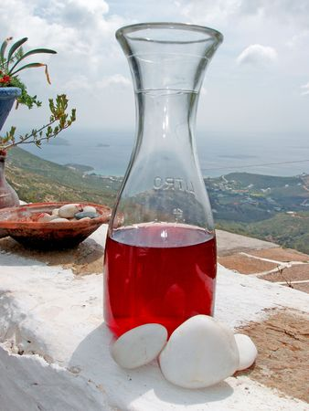 Red wine jar (1 litre) with view - Andros island, Greece Stock Photo