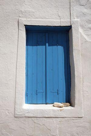 La ventana griega tradicional con los obturadores de madera azules para guardar el sumemr calienta hacia fuera. Paros, Grecia