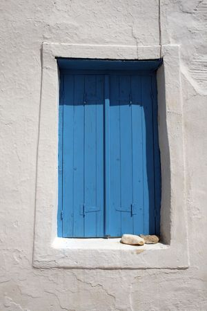 Traditional greek window with blue wooden shutters to keep the sumemr heat out. Paros, Greece