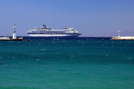 A large cruise ship passing by the entrance of the old harbor of Mykonos, Greece Stock Photo - 2017683