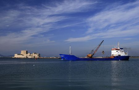 nauplio: Cargo ship with loaded crane passing in front of Mpourtzi fort - Nauplio, Greece