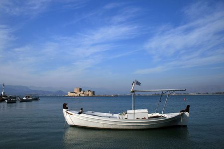 nauplio: Traditional greek fishing boat with view of fort Bourtzi on the background - Nauplio, Greece