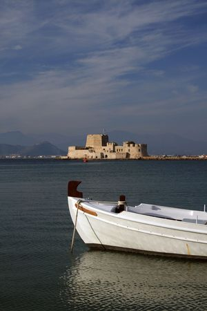 nauplio: Fort Bourtzi protecting the entrance to the harbor of Nauplio, the old capital of Greece, and a traditional greek fishing boat. Stock Photo
