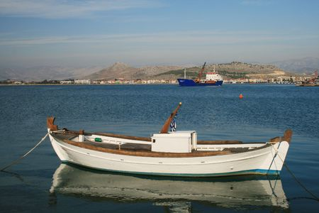 nauplio: Traditional greek fishing boat with an old cargo ship in the background - Nauplio, Greece