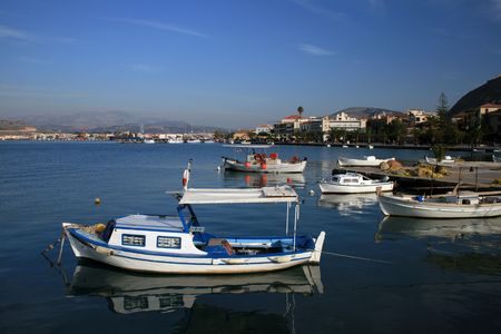 nauplio: Traditional greek fishing boat with view of the city of Nauplio in the background - Nauplio, Greece