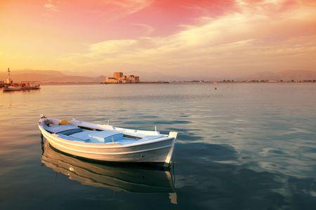 Barco de pesca griego tradicional con la vista de la fortaleza Bourtzi en el fondo - Nauplio, Grecia