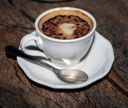 A cup of espresso coffee on a brown granite table