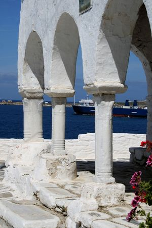 Architectural detail of a Byzantine Greek orthodox church situated above the harbor of Paroikia.  A ferry can be seen departing the island.  Paros Island, Greece Stock Photo - 2801012