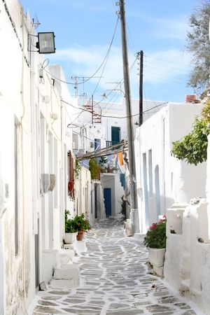 whitewashed: A traditional greek island narrow street sourrounded by whitewashed homes. Town of Paroikia.  Paros Island, Greece