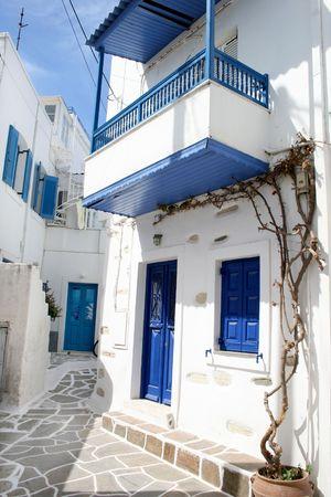 Un griego tradicional de la isla calle estrecha sourrounded de casas blancas. Ciudad de Paroikia. La isla de Paros, Grecia