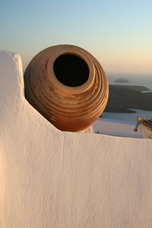Greek island of Santorini.  View of a terracota urn on a  home from the town of Fyra (Fira).  The volcano can be seen in the background. Greece Stock Photo