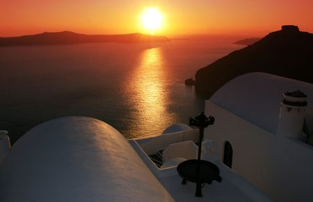 Greek island of Santorini.  Sunset view of whitewashed homes of the town of Fyra (Fira) built on the volcanic cliffs of the island. IN the background the volcano. Greece Stock Photo