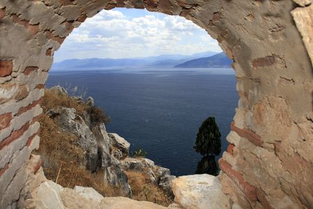 nauplio: View of the Peloponnese coast and Aegean sea from a guard hole of Palimidi fort. Palamidi is a military fortress to the east of  the town of Náfplio in the Peloponnese region of southern Greece