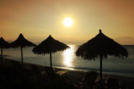 Beach umbrellas at the island of Aggistri, Greece photo
