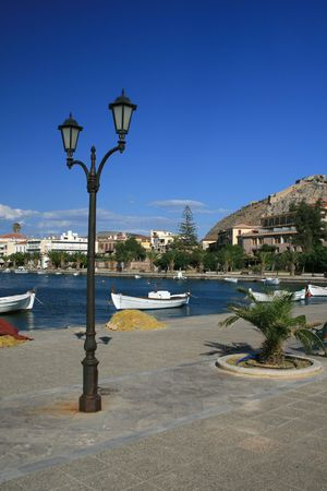 nauplio: Traditional greek fishing boat with view of the harbor and town of Nafplio in the background - Nauplio, Greece