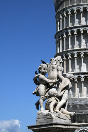 Statue and the famous leaning tower of Pisa, Italy photo