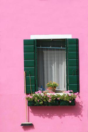 Pintado de color rosa brillante pared y ventana con un florero en la isla de Burano, cerca de Venecia, Italia