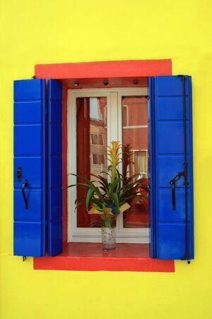 Brillante pared pintada en amarillo y una ventana de una casa en la isla de Burano