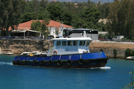Tug boat at the Corinth Canal in Greece used to guide ships through the channel crossing Stock Photo