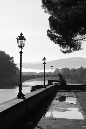 Black and white photo of the Arno river at dawn in Florence, Italy