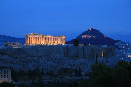 The Parthenon and the Acropolis with the city of Athens in the bacground at night, Greece