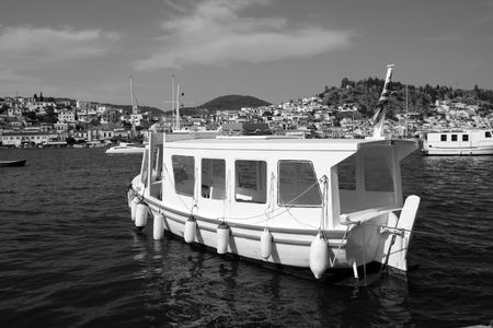 View of Poros island, Greece and small transport boat in black and white Stock Photo