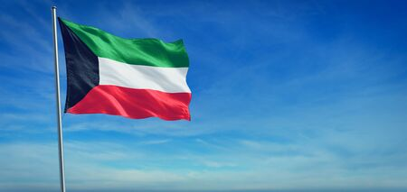The National flag of Kuwait blowing in the wind in front of a clear blue sky