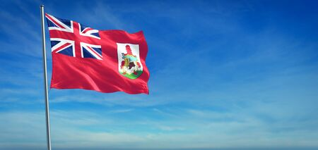 The National flag of Bermuda blowing in the wind in front of a clear blue sky Imagens