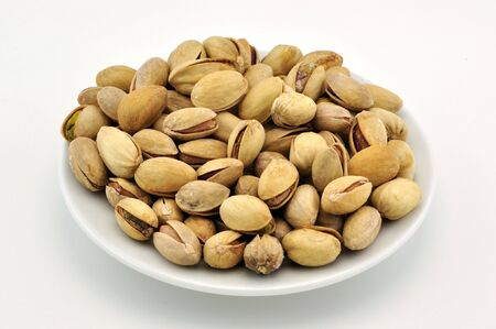 Pistachio nuts on white plate