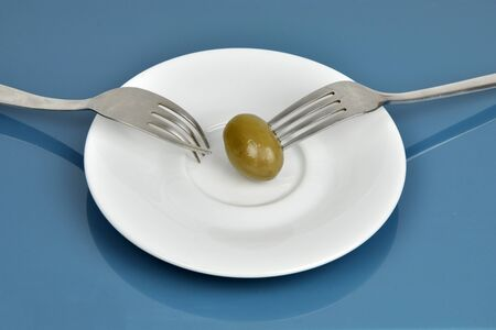 Two forks struggling about last olive on plate Stock Photo