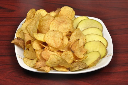 Raw potato and chips on white background