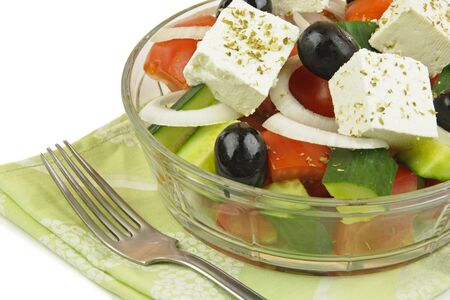 Greek mixed salad with fresh vegetable in glass plate on white background