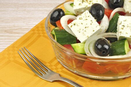 Greek mixed salad with fresh vegetable in glass plate on wooden background