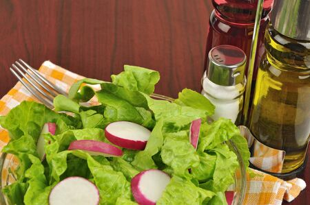 Mixed salad with lettuce and radish on wooden background close up
