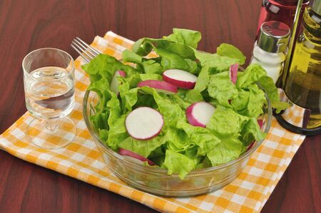 Mixed salad with lettuce and radish on wooden background