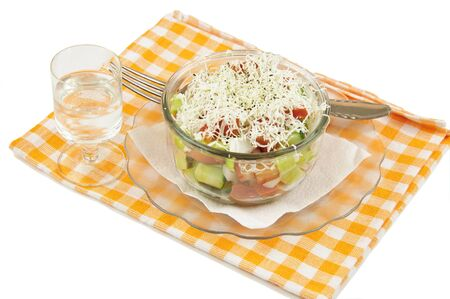 Shopska mixed salad in glass plate,ouzo and napkin on white