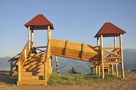 A wooden kids playhouse on top of the hill