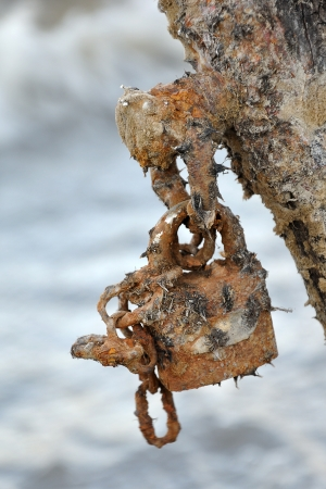 Rusted padlock against blurred water surface - outdated security and antivirus software metaphor