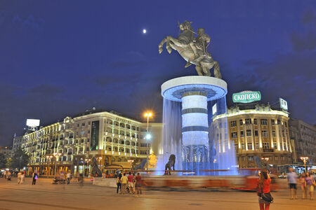 SKOPJE, MACEDONIA - JULY 17: Square Macedonia and the central fountain with monument called 'Voinot na konj' on July 17, 2013. Bronze statue of Warrior riding a horse and illuminated fountain at Skopje City Square in Skopje, Macedonia.