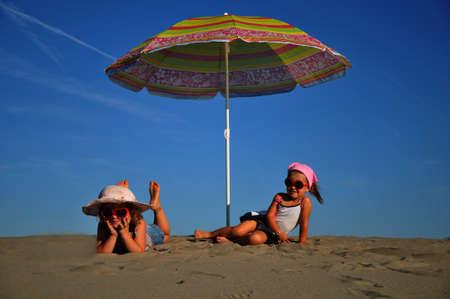 two beautiful girls lying under beach umbrellas photo