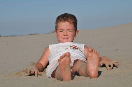 beautiful little boy lying on the sand photo
