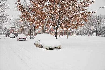 Cars parked on a city street covered with snow after a heavy sno
