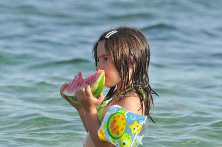 Girl eating watermelon on seashore