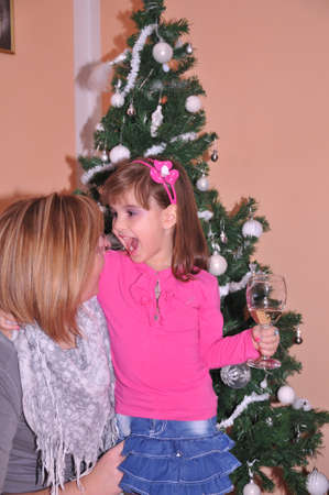 little girl with her mother in front of Christmas tree photo