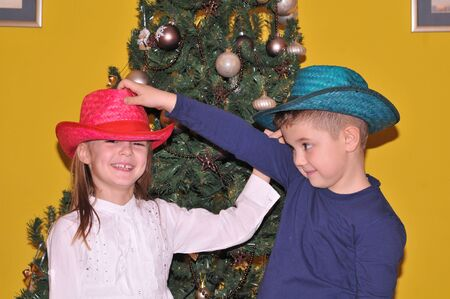 small children next to a Christmas tree photo