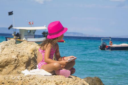 Little girl with tablet on beach during summer vacation