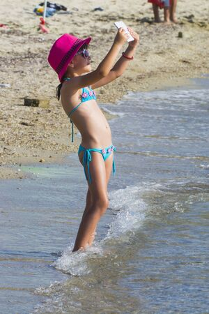 Little girl with tablet on beach during summer vacation Reklamní fotografie - 90298761