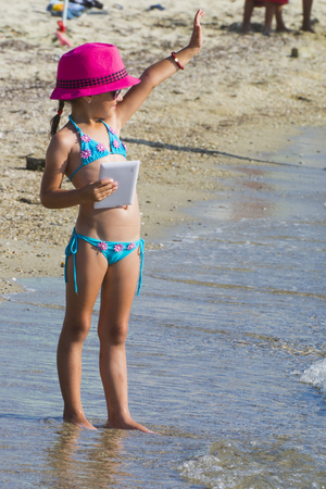 Little girl with tablet on beach during summer vacation Reklamní fotografie - 90298762
