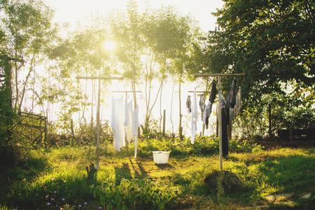 Frisch gewaschene Wäsche, die an einem warmen, sonnigen Tag draußen im Hinterhof des Bauernhofs an der Schnur trocknet