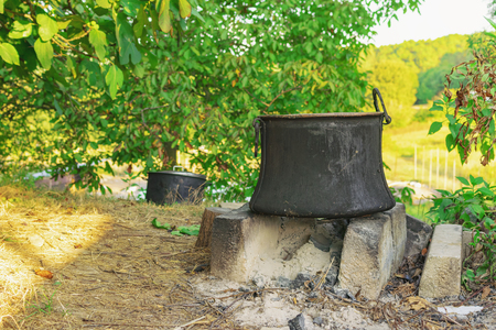 Old copper pot for cooking standing on concrete bricks on top of fireplace in the backyard